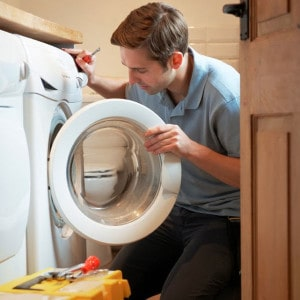 stock photo of person looking into front loading washing machine with screwdriver in hand and tool box on floor