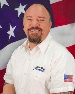 plumber named matt wearing white shirt sitting in front of American flag background