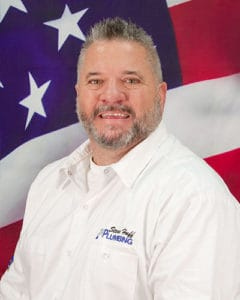 plumber named wade wearing white shirt sitting in front of American flag