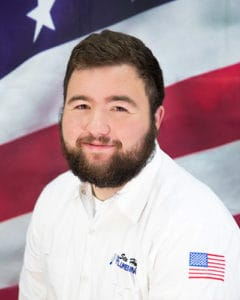 plumber in white shirt in front of American flag