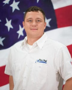 plumber in white shirt sitting in front of American flag