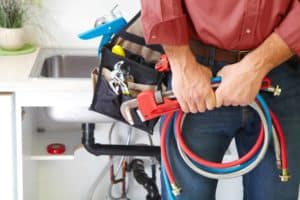 plumber holding tools and tool bag